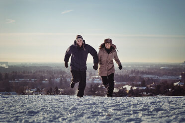 Full length of happy couple running on snow covered mountains - MASF03606