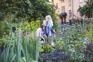 Daughter kissing mother while gardening on field - MASF03651