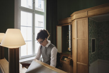 Female lawyer standing at desk in library - MASF03666