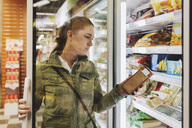Female customer reading product seen through glass door at refrigerated section - MASF03669