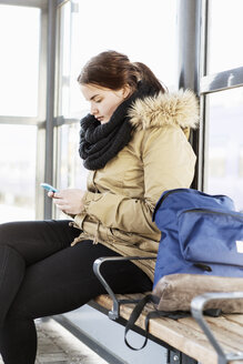 Young woman using mobile phone on bench at train station - MASF03672