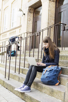 Young woman using laptop on steps of high school - MASF03675