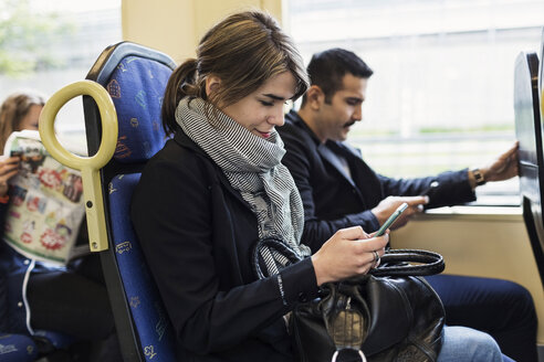 Young woman using mobile phone while sitting with man in tram - MASF03678