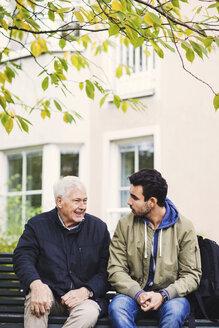 Caretaker communicating with senior man while sitting on bench - MASF03687