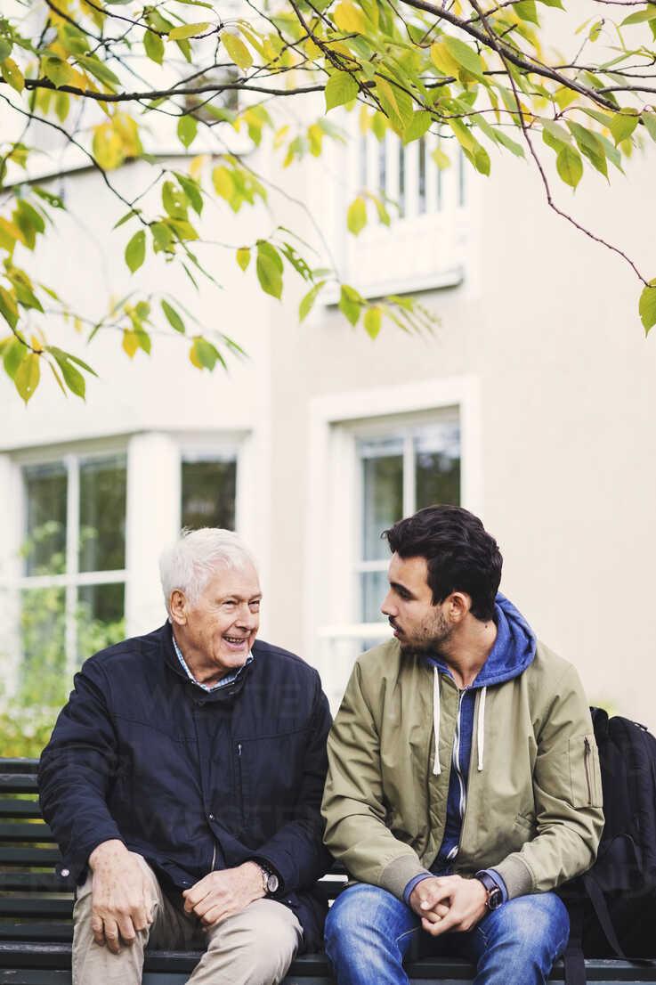 Caretaker communicating with senior man while sitting on bench - MASF03687 - Maskot ./Westend61