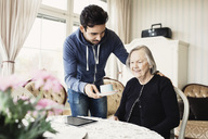 Caretaker serving coffee to senior woman sitting at nursing home - MASF03690