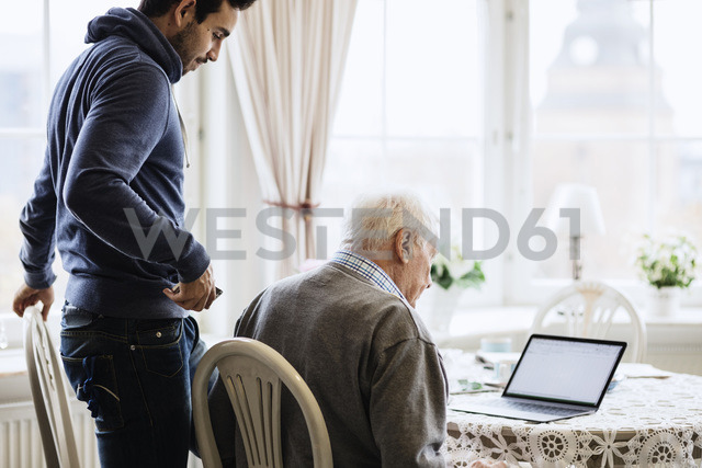 Caretaker and senior male using laptop at dinning table - MASF03696