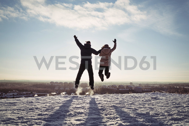 Couple holding hands while jumping on snow covered mountain against sky - MASF03705 - Maskot ./Westend61
