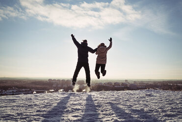 Couple holding hands while jumping on snow covered mountain against sky - MASF03705