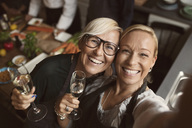 Cheerful mature women holding champagne flutes while taking selfie in kitchen - MASF03732