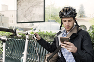 Male commuter using smart phone while sitting at bus stop - CAVF38037