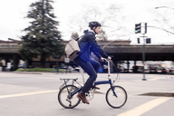 Side view of businessman riding bicycle on city street - CAVF38040