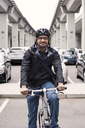 Portrait of smiling businessman sitting on bicycle with bridges and parking lot in background - CAVF38046
