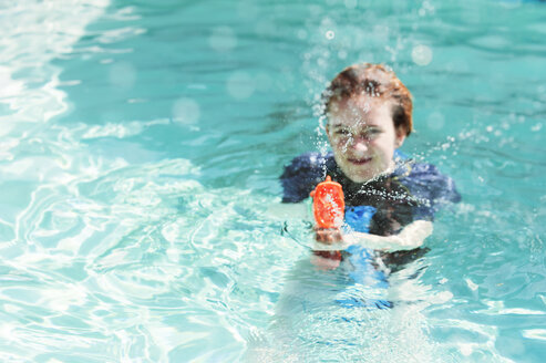 Portrait of teenage girl playing with squirt gun in swimming pool - CAVF38070