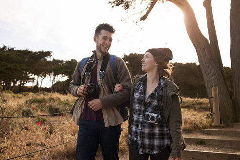 Happy hiking couple walking on field - CAVF38106