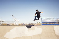 Low angle view of man performing stunt in skateboard park - CAVF38184