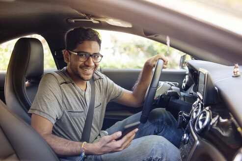 Portrait of smiling man with mobile phone traveling in car - CAVF38196