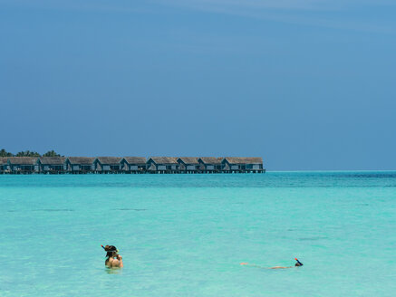 Maledives, Ross Atoll, snorkeler and water bungalows in the background - AM05690