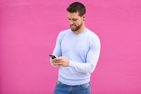 Young man texting with smartphone, pink background - JSMF00141