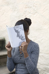 Woman covering face with book, reading poetry in front of wall - PSTF00098