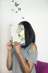 Woman covering face with book, reading poetry with butterflies - PSTF00101