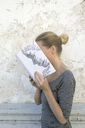 Woman covering face with book, reading poetry in front of wall - PSTF00104