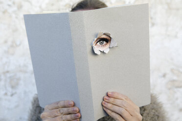 Woman covering face with book, reading poetry, eye looking through cover - PSTF00107