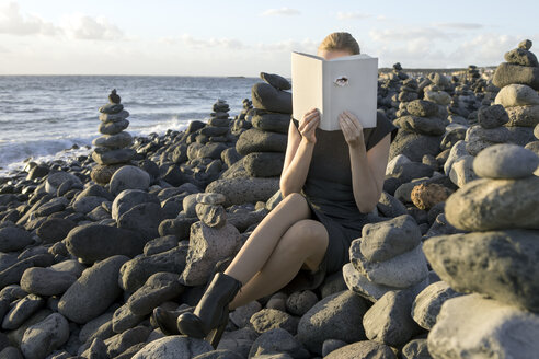 Woman covering face with book, reading poetry, eye looking through cover - PSTF00110