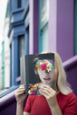 Woman covering face with book, reading poetry - PSTF00113