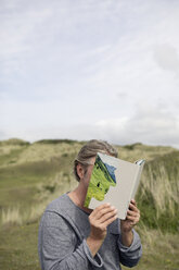 Man covering face with book, reading poetry in the dunes - PSTF00116