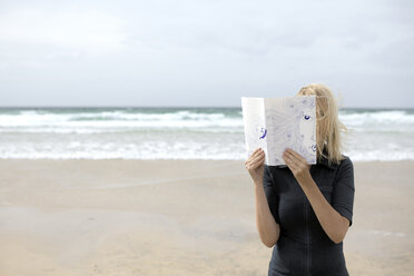 Woman covering face with book, reading poetry on beach - PSTF00119