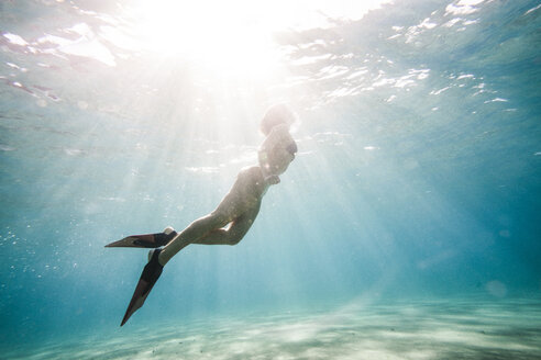 Low angle view of woman swimming in sea - CAVF38275