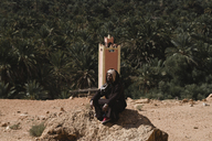 Man with eyes closed wearing traditional clothing while sitting on rock against palm trees at Sahara Desert - CAVF38284