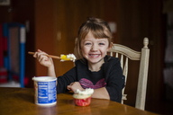 Portrait of happy girl eating cupcake at home - CAVF38290