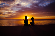 Silhouette siblings sitting by beach during sunset - CAVF38314