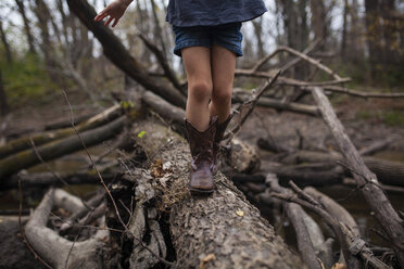 Low section of girl walking on tree trunk in forest - CAVF38320