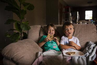 Happy siblings eating bread on sofa - CAVF38326