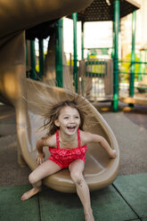Happy girl playing on slide at playground - CAVF38329