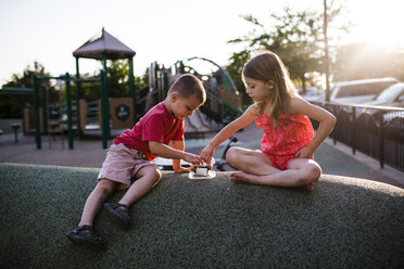 Siblings eating food in playground during sunset - CAVF38332