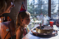 Girl looking at birthday cake with mother at home - CAVF38335