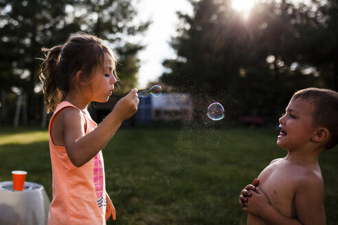 Boy looking at sister blowing bubble at backyard - CAVF38341