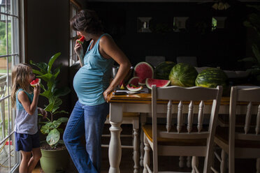 Mother and daughter eating watermelon at home - CAVF38350