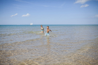 Playful siblings running in sea against sky on sunny day - CAVF38362