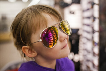 Close-up of girl wearing sunglasses at shop - CAVF38374