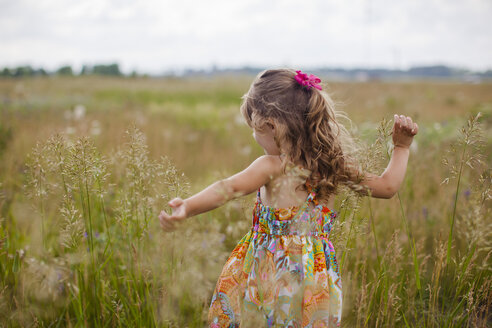 Girl with arms outstretched playing on grassy field - CAVF38377