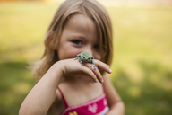 Portrait of playful girl with frog standing in yard - CAVF38383