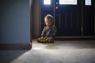 Cute boy playing with toy on floor at home - CAVF38386