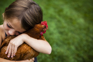 High angle view of cute girl embracing hen at yard - CAVF38392