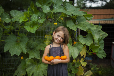 Portrait of smiling girl holding pumpkins while standing against plants - CAVF38401