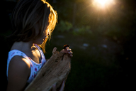 Side view of girl holding caterpillar and wood in yard during sunset - CAVF38413